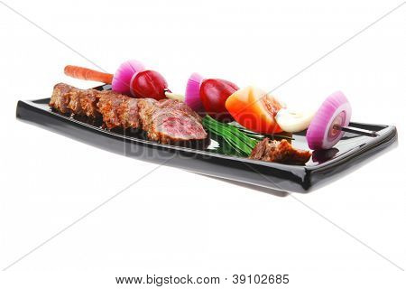main course : roast red meat slices served on black plate with vegetables on spit isolated on white background