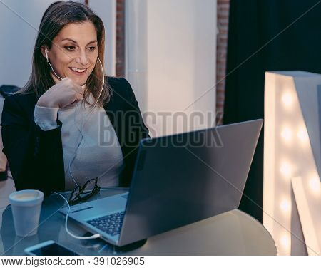 Adult Female Freelancer Using Laptop Computer For Video Conference While Sitting In Modern Coffee Sh