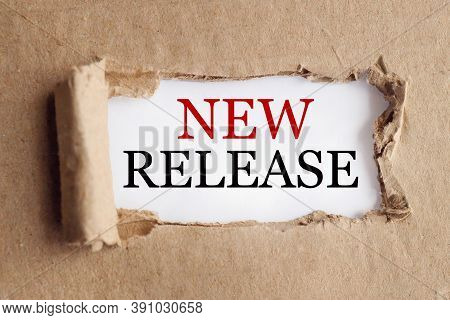 The Text New Release Appearing Behind Torn Brown Paper