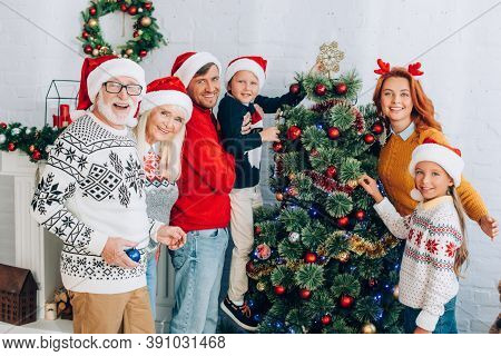Family In Santa Hats Smiling At Camera While Standing Near Christmas Tree Together