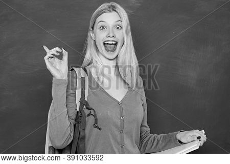 Happy Girl Holding Book And Looking At Camera While Standing In Classroom. Student With Backpack. Lo