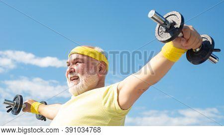 Senior Man Lifting Dumbbell. Portrait Of Healthy Happy Smile Senior. Senior Sportsman In Sport Cente