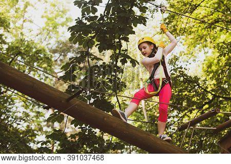 Child Boy Having Fun At Adventure Park. Child Climbing On High Rope Park. Happy Little Child Climbin