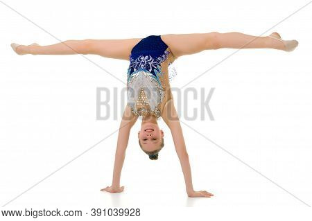 A Slender Girl Gymnast, In A Beautiful Gymnastic Leotard For Competitions, Performs A Handstand. Con