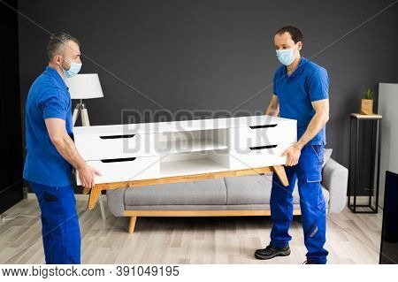Professional Movers Moving Tv Console Furniture In Face Mask