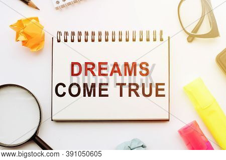Dreams Come True Text On Notebook With Office Tools