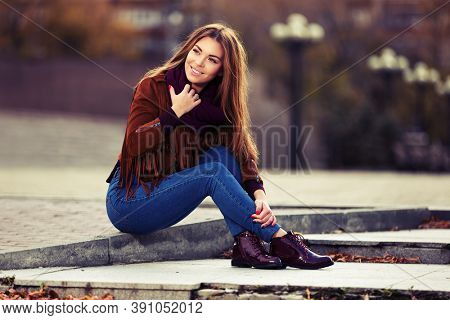 Happy young fashion woman sitting on street sidewalk  Stylish female model in red leather fringe suede jacket and dark blue jeans