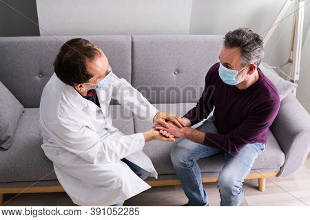 Doctor And Senior Patient Living In Assisted Home With Face Mask