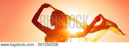 Beautiful woman happy free in summer sunset glow waving scarf in the wind dancing in sun panoramic banner. Silhouette feminine lady freedom for wellness and healthy living.