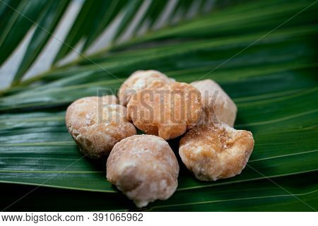 Organic Brown Palm Sugar Or Coconut Sugar On Green Coconut Leaves. Sweet Sugar Made From Coconut Flo