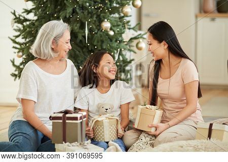 Asian Mother And Her Daughter With Granddaughter Congratulating Each Other With Christmas And Giving