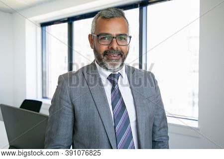 Content Indian Ceo Standing And Smiling For Portrait. Successful Pensive Bearded Businessman In Glas