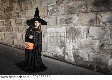 Young Girl Dressed In A Witch Costume With Tall Black Hat And Holding A Pumpkin Pail For Halloween.