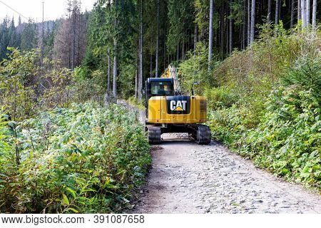 Tatra Mountains, Poland, 23/09/2020. Yellow Excavator Driving On A Mountain Trail In Coniferous Fore