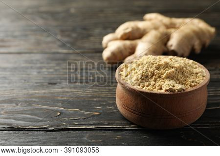 Ginger And Bowl With Ginger Powder On Wooden Background
