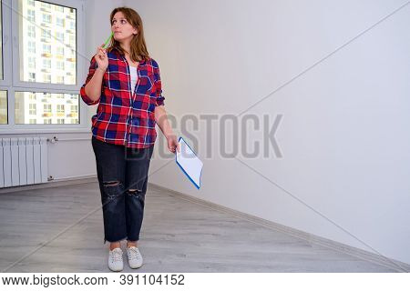 Inspection In A Plaid Shirt Of The Apartment In The New House For Purchase Or Identification Of Defe