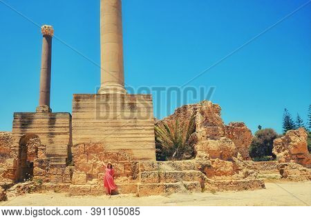 Woman On The Background Of Ancient Roman Columns, The Ruins Of Anthony Terms. Archaeological Excavat