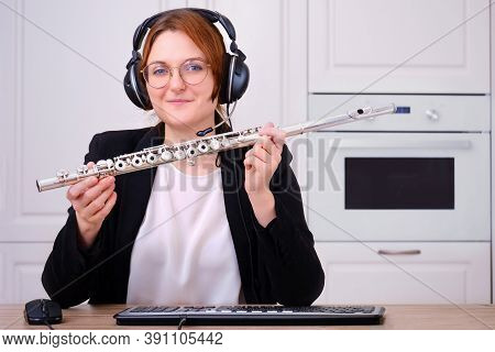 A Music Teacher Provides Online Training In Playing The Flute. A Female Flautist Teaches A Flute Les