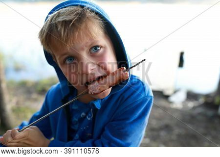 Child Eating Sausage On Skewer By Lake
