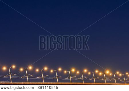 Bridge Lampposts At Night. Beautiful Yellow Light Of Road Poles. Minimal Night Photography, Copy Spa
