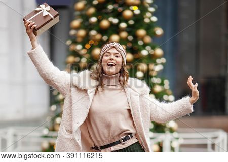 Happy Young Woman Holding A Gift On A Christmas Market. Time To Give Gifts. Concept Of Christmas Sho