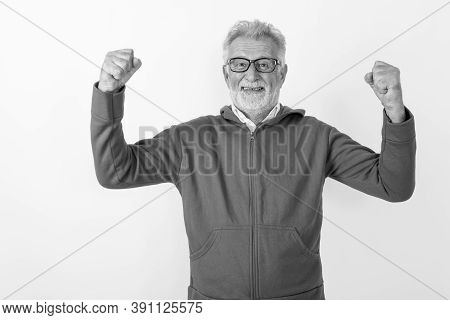 Studio Shot Of Happy Senior Bearded Man Smiling While Flexing Both Arms Ready For Gym Against White