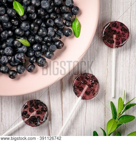 Homemade Lollipops Made From Natural Dehydrated Bilberry On A White Wooden Background. Healthy Vegan
