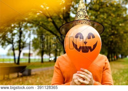 Man In An Orange Sweater And A Black Witch's Hat Holds A Red Pumpkin Balloon With An Evil Face Again