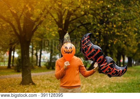 Man In An Orange Sweater And A Black Witch Hat Holds A Red Pumpkin Balloon With An Evil Face And A B