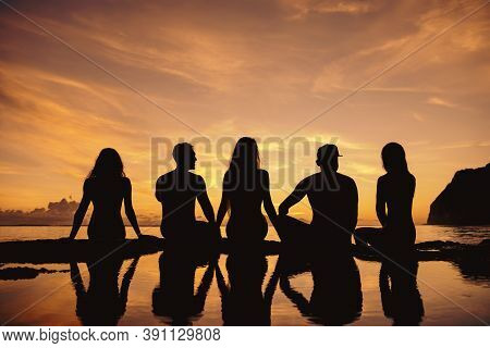 Group Of Friends Are Sitting At Sea Beach And Enjoys Sunset
