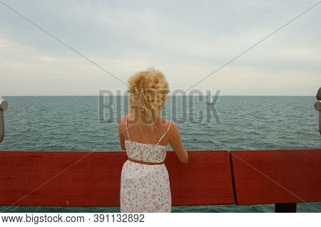 Young Curly-haired Girl, On The Pavement By The Lake, Looking Into The Distance Of The Lake, White D