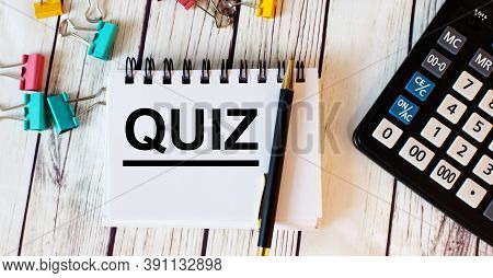 On A Light Wooden Table Lies A Calculator, Multi-colored Paper Clips And A Notebook With A Pen And T