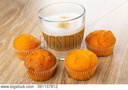 Few Orange Muffins Around Transparent Glass With Latte-macchiato On Wooden Table