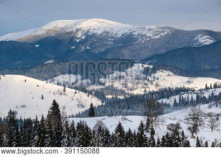 Small Alpine Village And Winter Snowy Mountains In First Sunrise Sunlight Around, Voronenko, Carpath