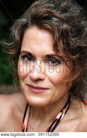 An Outdoor Potrait Of A Naturally Beautiful Mature Woman Looking At The Camera