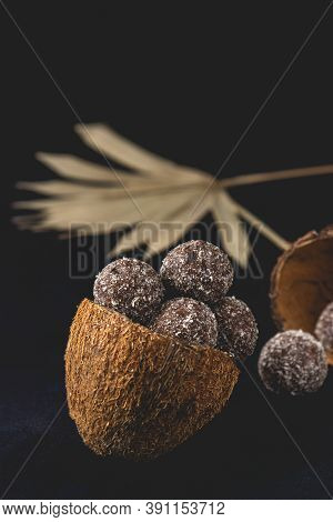 Coconut Healthy Sugar Free Bliss Balls In Coconut Shells Placed On Dark Background. Close-up View.