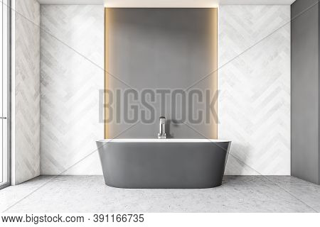 Grey Bathtub With Faucet Against Grey Wall And Tile Decoration On The Sides. Yellow Backlight In A B