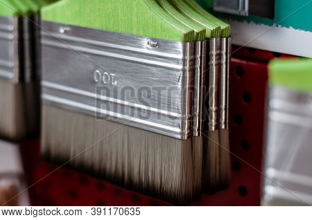 Extreme Close-up Of Hanging Paintbrushes With Green Wooden Handles In An Artisan Tool Shop