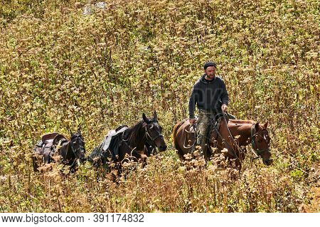 Adygea, Russia - September 08, 2020: Rider Climbs The Mountain Along The Slope Overgrown With Autumn