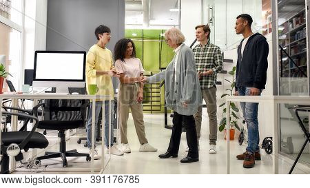 Full Length Shot Of Cheerful Young Team Greeting New Employee, Aged Woman, Senior Intern At Her New
