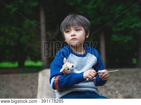 Emotional Portrait Of Lonely Kid Hugging Dog Toy Sitting Alone In The Playground, Sad Child Sitting