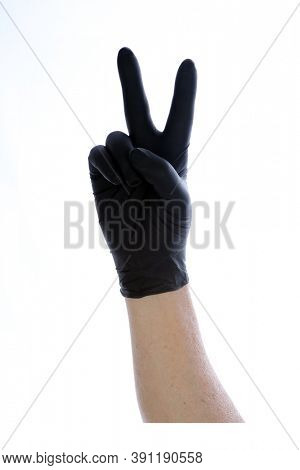 Peace Sign with Latex Gloves. A Caucasian mans hand makes a Peace Sign or Victory Sign while wearing a disposable Black Latex glove. Isolated on white. Room for text.