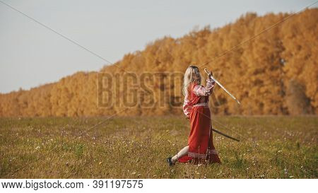 Militant Woman In Red National Dress Training Her Swordplay On Autumn Field