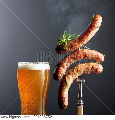 Beer And Grilled Bavarian Sausages. Juicy Steaming Sausages On A Fork Sprinkled With Rosemary. Copy