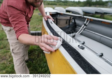 Man Hand Diligently Wipes The Kayak From Water Drops After A Walk, On The Lawn Against The Backgroun