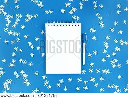 White Blank Sheet Of Notebook And A Pen On A Blue Background With Scattered Confetti Snowflakes. Hol
