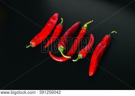Fresh Chili Peppers Of Red Color Evenly Arranged On A Black Background.