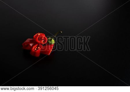 Fresh Chili Peppers, Cut Into Pieces, Lie On A Black Background. Copyspace