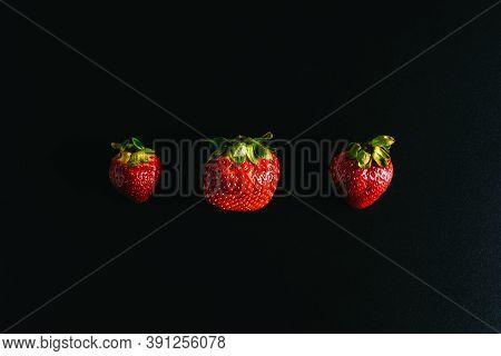 Three Juicy Strawberries Lie On A Black Background