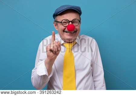 Portrait Of A Senior Cheerful Man With Red Nose Pointing Up Giving Advice.